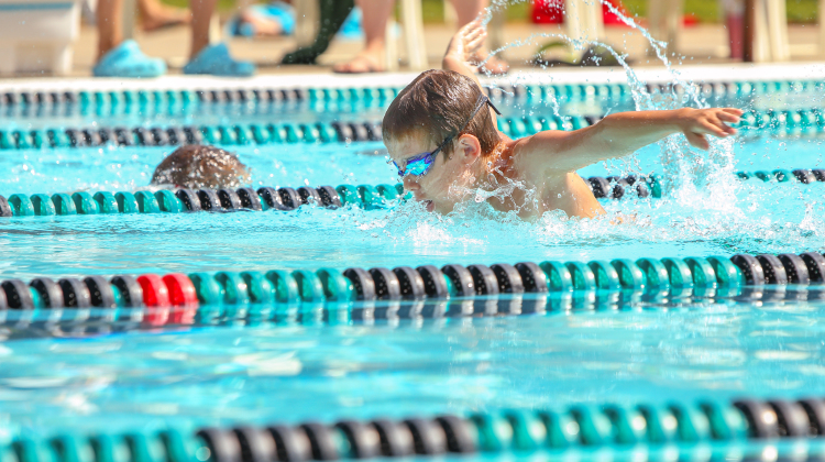 Boy swimming Butterfly in a race. Focus on face and water drops,
