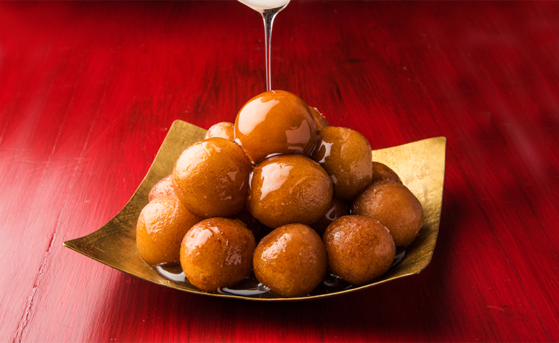 Gulab Jamun served in a square brass plate with pouring sweet sy