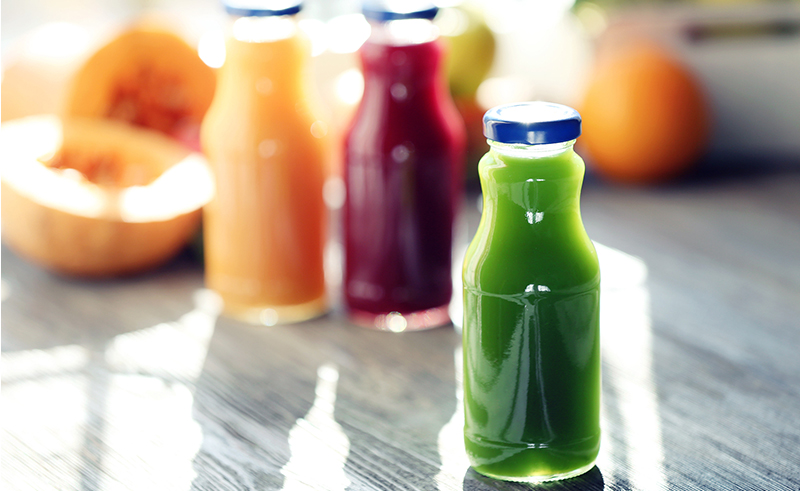 Bottles of juice with fruits and vegetables on windowsill close