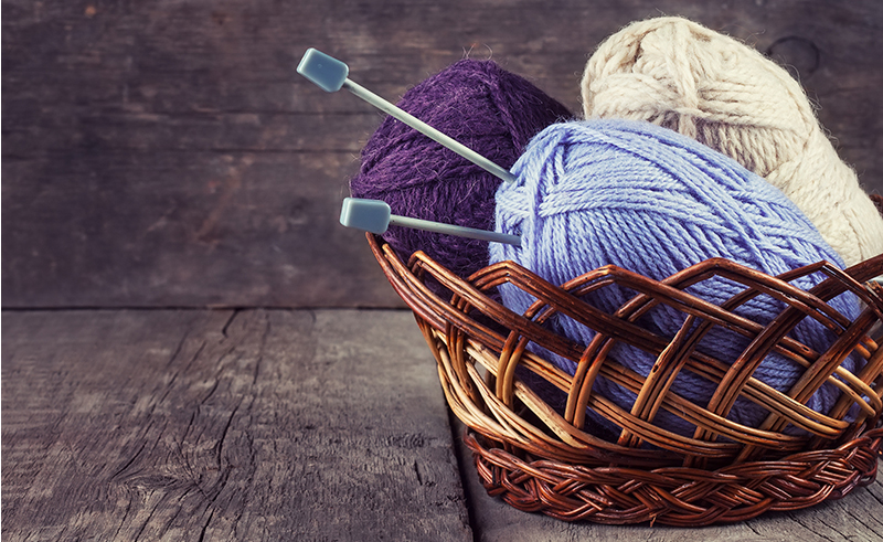 Skeins colored yarn and knitting needles in a basket on a wooden background